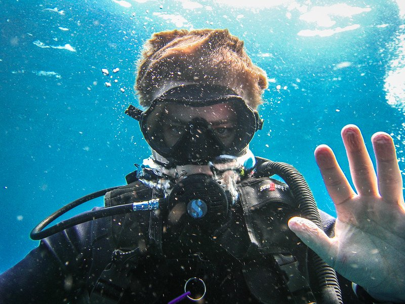 young diver on holiday in malta waving to camera